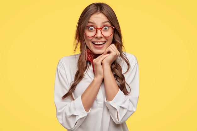 かなり満足している女性は、良い気持ちを表現し、あごの下で手をつないで、幸せそうな顔をして、特大の白いシャツを着て、黄色い壁に隔離されているように表現します。人と喜びのコンセプト