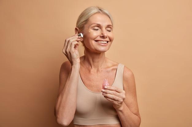 Довольно довольная зрелая женщина наносит косметическую сыворотку на лицо, имеет блестящую здоровую кожу, закрывает глаза с удовлетворением, держит пипетку с молочной кислотой