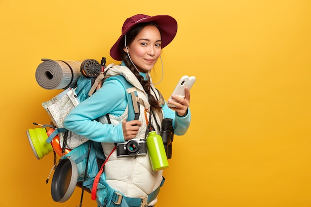 Довольно довольный путешественник использует бесплатное подключение к интернету на смартфоне для ведения блога во время путешествия по путешествиям, несет большой тяжелый рюкзак
