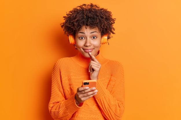 꽤 만족 한 여자가 정면에서 부드럽게 미소 짓고 입술 근처에 손가락을 유지하며 온라인 문자 메시지에 스마트 폰을 사용하고 음악을 듣고 스테레오 무선 헤드폰을 착용합니다.