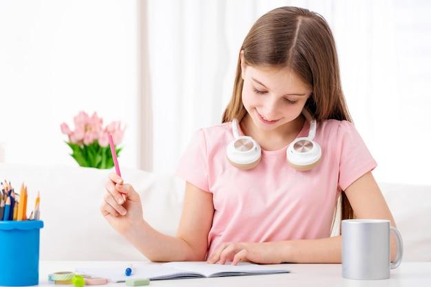 Милая школьница делая домашнее задание дома