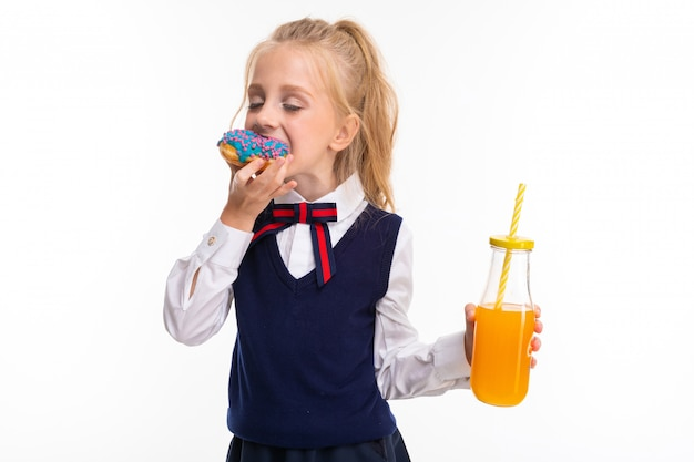 Pretty schoolgirl eats a donut and drinks juice isolated on white