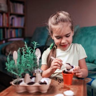 卵殻、ロスマリー、タイム、ゼロウェイストガーデニングのコンセプト、温室、健康的なライフスタイルでキッチンハーブを育てるかわいい女子高生