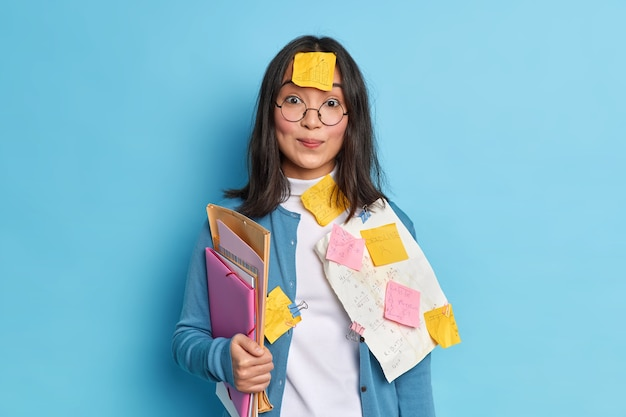 Pretty schoolgirl prepares for math test crams material has sticker on forehead not to forget necessary information busy studying.