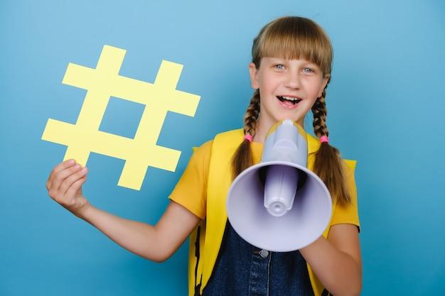 예쁜 여학생은 확성기로 비명을 지르며 큰 해시태그 기호를 들고 노란색 배낭을 메고 스튜디오에서 파란색 배경 위에 고립된 포즈를 취합니다. 트렌디한 소셜 미디어의 개념입니다. 모의 복사 공간