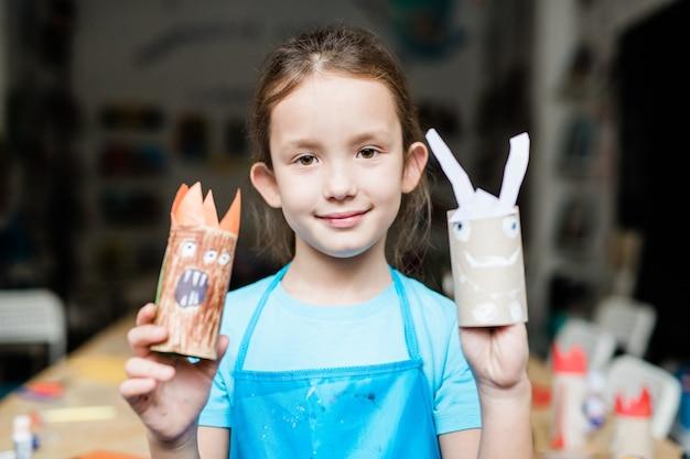 Симпатичная школьница показывает страшные хэллоуинские игрушки ручной работы из свернутой бумаги в школе перед праздником