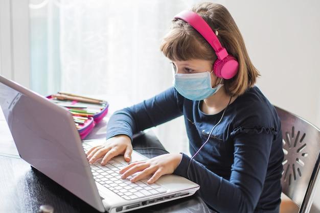 自宅でのオンラインレッスン中に宿題の数学を勉強しているかわいい女子高生、検疫中の社会的距離、