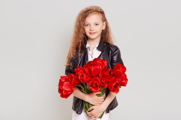Pretty schoolgirl with wavy blonde hair wearing leather jacket standing with red tulips in hands and looking directly at front with cute expression