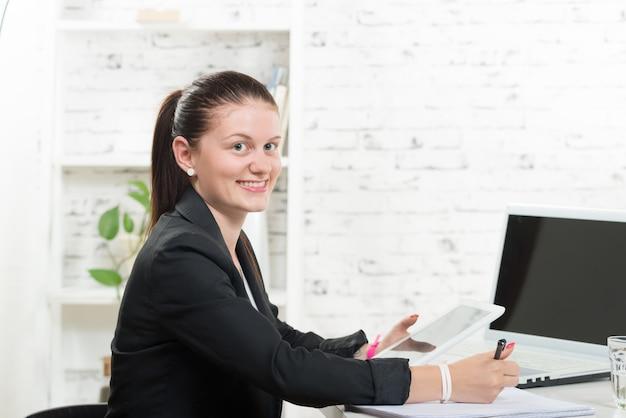 A pretty secretary looking at a digital tablet