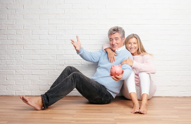 Pretty senior couple sitting on thier house floor with a piggy b