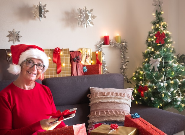 A pretty senior lady happy for the new tablet just received as a christmas present. holiday day for a retired people. she smiles while sitting on the sofa.