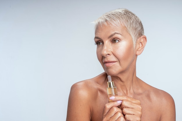 Pretty senior lady holding face serum in her hand to her face