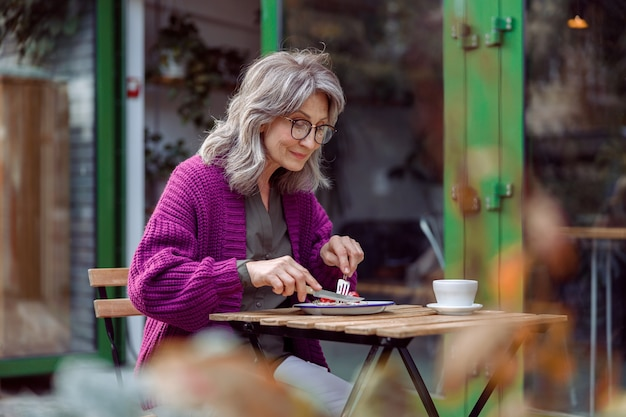 Pretty senior lady in purple knitted jacket eats delicious dessert at table on outdoors cafe terrace