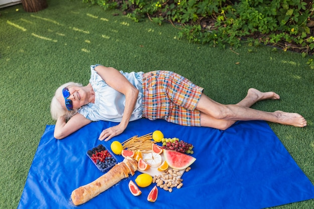 Pretty senior woman enjoy pic-nic and relaxing outdoors