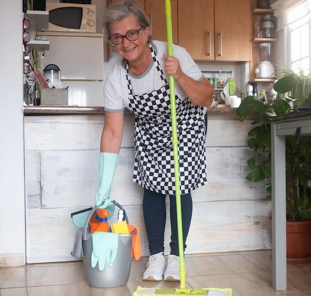家事を始める準備ができているかなり年配の女性。彼女の近くには、掃除用のアイテムが入ったプラスチック製のバケツがあります。白と黒の市松模様のエプロンを持った一人の人