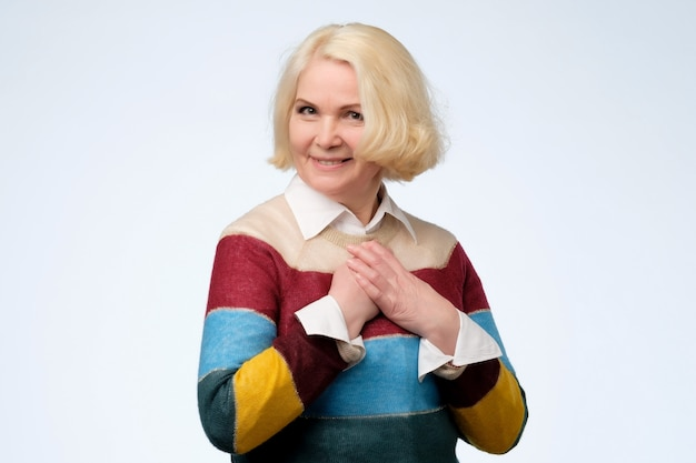 Pretty senior woman wearing colored sweater is touched with compliment