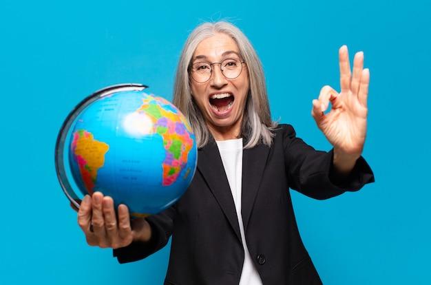 地球儀を持つかなり年配の女性。世界のコンセプト