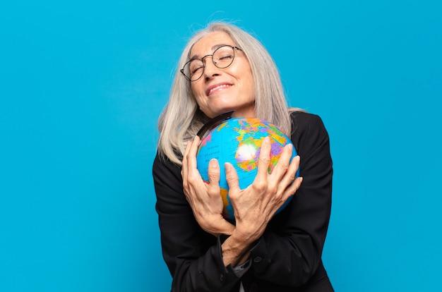 Довольно старшая женщина с земным шаром. мировая концепция