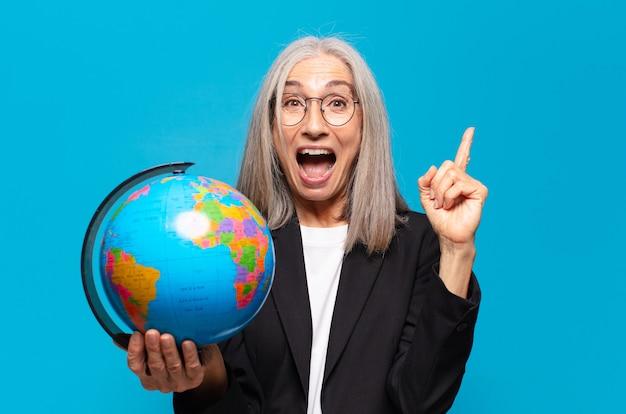 地球儀を持つかなり年配の女性。世界の概念