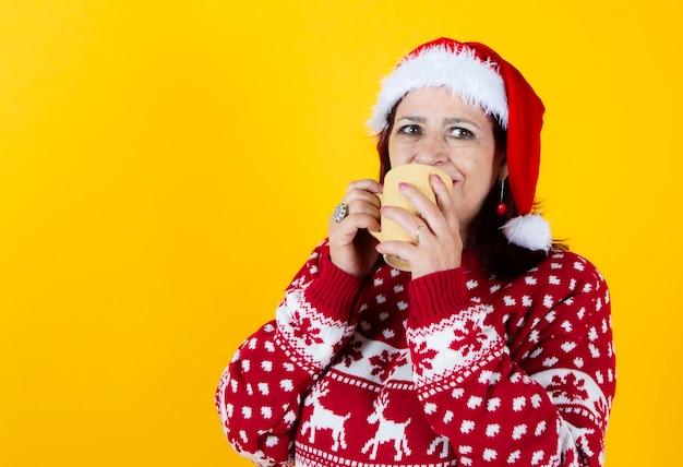 Pretty senior woman with christmas clothes drinking coffee, yellow background