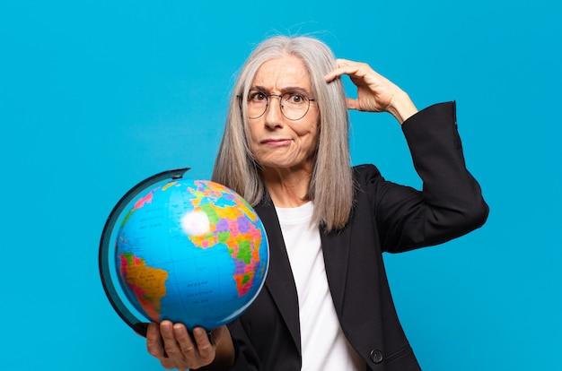 Pretty senior woman with a earth globe. world concept