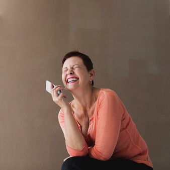 Pretty senior woman with phone laughing