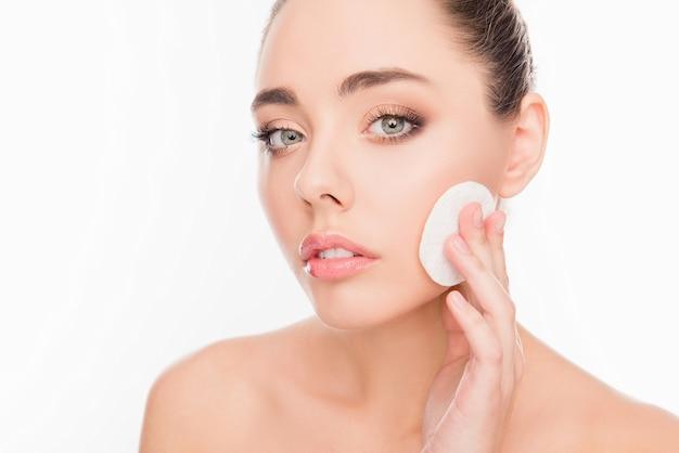 かなり敏感な女の子はコットンパッドで化粧を洗い流します