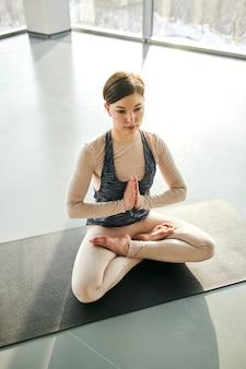 ジムでのヨガの練習中にマットの上に座っている間、手を合わせて足を組んでいるスポーツウェアのかなり穏やかな女の子