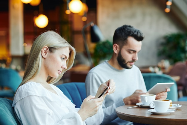Pretty serious blonde girl and her boyfriend sitting by table in cafe, having drinks and using mobile gadgets at leisure