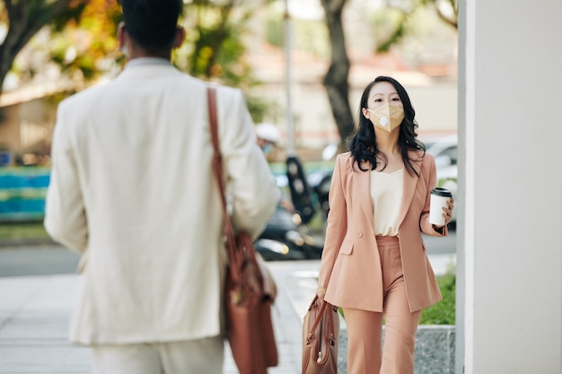Pretty serious young asian businesswoman in protective mask going to work in the morning with take out coffee in hands