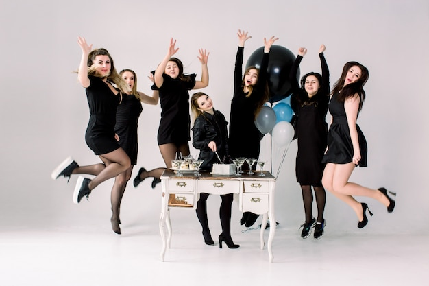 Pretty seven girls in black dresses, celebrating birthday or hen party, standing and jumping near the decorated table with cake, drinks, desserts and with balloons