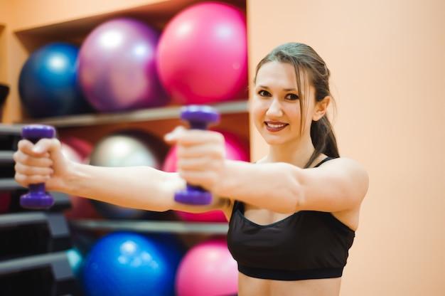 屋内スポーツホールのトレーニングで大きなボールの上に横たわる筋肉質のボディを持つかなり性的なストレートフィットネス女性。
