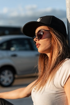 Pretty sexy american girl in black fashion cap in vintage sunglasses in summer clothes resting on street in sunny day. portrait beautiful sexy girl on parking outdoors at sunset.