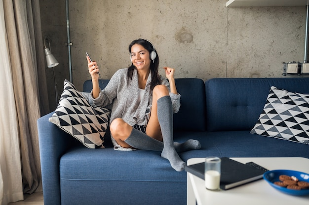 Pretty sexy smiling woman in casual outfit sitting in living room listening to music on headphones, having fun at home
