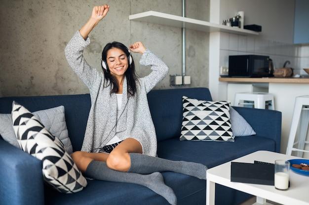 Довольно сексуальная улыбающаяся женщина в повседневной одежде сидит в гостиной, слушает музыку в наушниках, развлекаясь дома