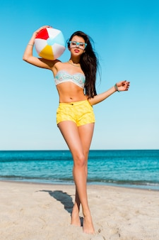 Pretty sexy sportive tan woman playing ball  on the summer beach . wearing yellow shirts, colorful  top and cool glasses.