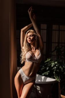 화창한 아침에 욕실에서 포즈를 취하는 세련된 흰색 속옷을 입은 아름다운 슬림 몸매를 가진 꽤 섹시한 젊은 열정 여성. 란제리의 패션 컬렉션