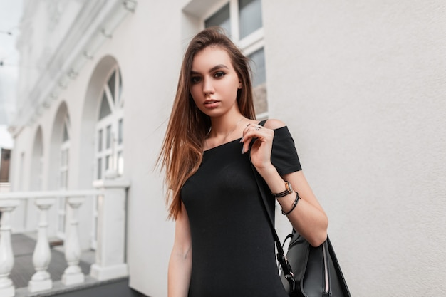 Pretty sexy young woman model in an elegant black dress with a leather stylish black backpack travels around the city. attractive fashionable girl enjoys a walk on a street. street youth style.