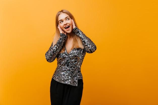 幸せな笑顔でポーズをとるかなり格好の良い女性。エレガントなパーティー衣装でかわいいヨーロッパの女性の屋内の肖像画。