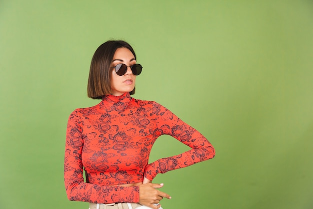 Pretty short hair woman with golden earrings, sunglasses, red china dragon printed blouse on green