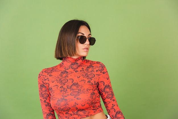 Bella donna dai capelli corti con orecchini dorati, occhiali da sole, camicetta rossa con stampa drago cinese su verde