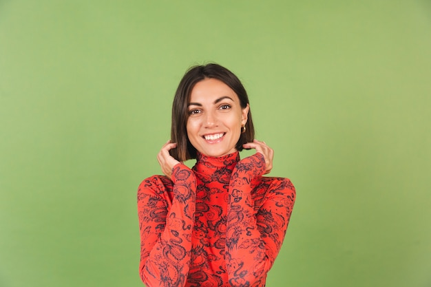 Pretty short hair woman with light make up golden earrings red china dragon printed blouse on green, positive emotions, confident smile
