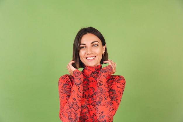 金色のイヤリングを作った明るいショートヘアの女性、緑に赤い中国のドラゴンがプリントされたブラウス、ポジティブな感情、自信に満ちた笑顔
