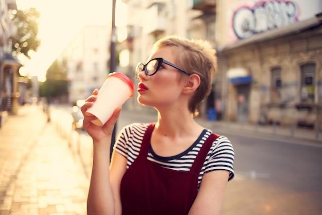 屋外でカップを飲むかなり短い髪の女性。高品質の写真
