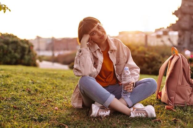 Una bella donna dai capelli corti in jeans e giacca rosa si siede sull'erba durante il tramonto