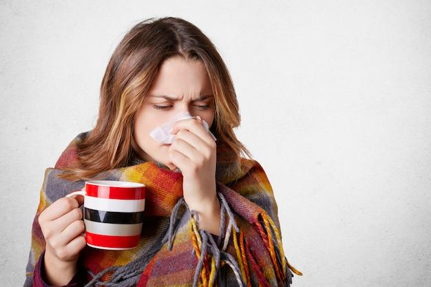 Довольно больная женщина имеет насморк, протирает нос платком, пьет горячий напиток, завернутый в теплое одеяло, имеет высокую температуру и холод, изолированные на белом