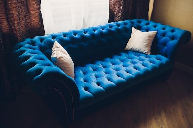 파란 소파와 빛이있는 거실의 아주 간단한 장식.