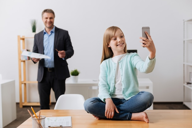 엄마에게 메시지를 보내고 아빠 사무실에서 하루에 대해 이야기하는 매우 진심 어린 소녀
