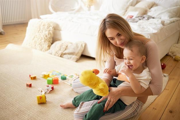 寝室の床に座って、弟と一緒に時間を過ごすかわいい妹。ぬいぐるみのアヒルを持って、屋内で小さな男の子と遊んでいる美しい若いベビーシッター。乳児期、育児、母性