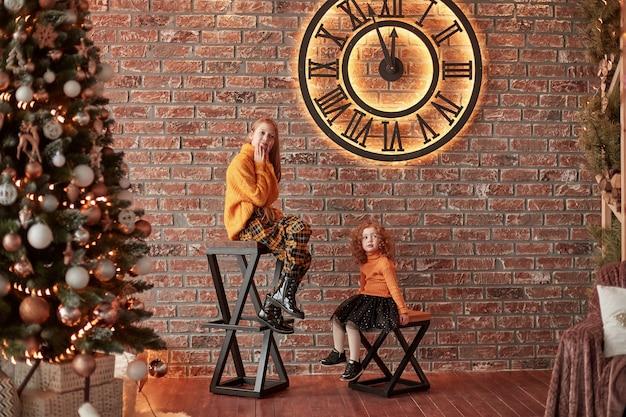크리스마스 이브에 세련된 거실에 앉아 예쁜 자매.
